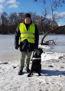 Förare och hund står framför kameran. I bakgrunden fruset vatten och en klarblå himmel.