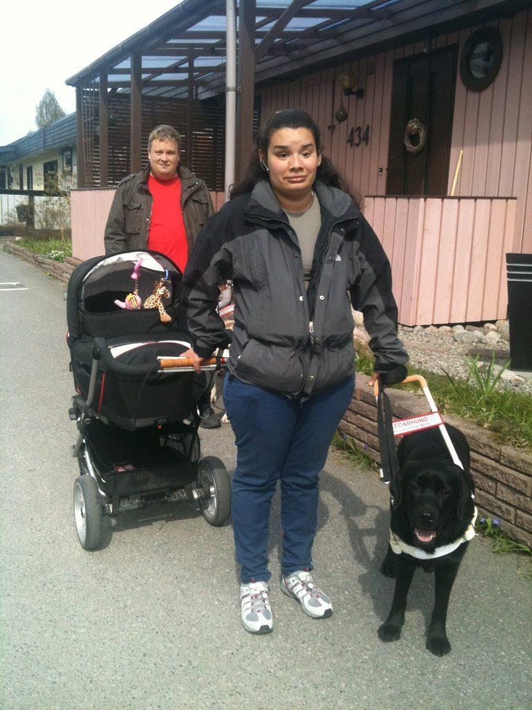 En kvinna står med en svart ledarhund. Hon håller i en svart barnvagn. Bakom henne syns en man.